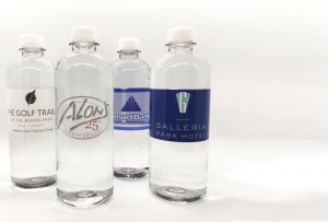 Four clear water bottles with custom labels